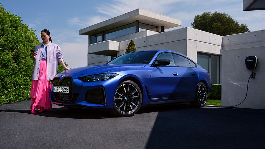 BMW i4 M50 G26 2021 BMW Individual Frozen Portimao Blau metallic Dreiviertel-Frontansicht stehend mit Frau vor Haus